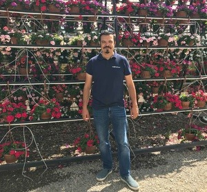 Can Erol posing in front of flowers hanging baskets Turkey